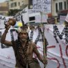 Photo - An indigenous man shouts as demonstrators march toward the Maracana stadium ahead of the Confederations Cup final in Rio de Janeiro, Brazil, Sunday, June 30, 2013.  Protesters have taken to the streets all over Brazil in the past two weeks, calling for a wide-range of reforms.  Public approval of Brazilian President Dilma Rousseff's government has suffered a steep drop in the weeks since massive protests broke out across the country, according to Brazil's first nationwide poll released since the unrest began.(AP Photo/Felipe Dana)