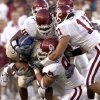 Lance Mitchell, back, Teddy Lehman, right, and Chris Chester tackle Eric Richardson of Tulsa during the OU Tulsa college football game Friday, August 30, 2002. Staff photo by Bryan Terry