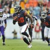 Photo - Chicago Bears cornerback Tim Jennings (26) runs after intercepting a pass intended for Minnesota Vikings wide receiver Jerome Simpson (81) during the first half of an NFL football game on Sunday, Sept. 15, 2013, in Chicago. (AP Photo/Jim Prisching)
