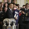 Photo - FILE - In this May 3, 2010 file photo, President Barack Obama is presented a Naval Academy football jersey with number 44 by Osei Asante, a senior from Houston, as the Naval Academy's 2009 football team was honored with the Commander In Chief Trophy for victories over rival military academies, in the East Room of the White House in Washington. The Defense Department said Tuesday, Oct. 1, 2013, it has temporarily suspended all sports competitions at the service academies as a result of the partial government shutdown. The decision jeopardizes this weekend's football games _ Air Force at Navy and Army at Boston College. (AP Photo/J. Scott Applewhite, File)