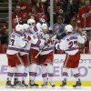 Photo - New York Rangers left wing Benoit Pouliot, second from right, celebrates his second period goal against the Detroit Red Wings with teammates John Moore (17),  J.T. Miller (10), Brian Boyle (22) and Ryan McDonagh (27) during an NHL hockey game Saturday, Oct. 26, 2013, in Detroit. (AP Photo/Duane Burleson)