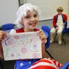 Cierra Phillips shows the sign she made to represent her character-- Betsy Ross. Phillips didn\'t realize she had transposed the \'s\' and the \'t\' in Betsy\'s name until someone brought it to her attention. Wearing authentic era attire, students in Rhonda Watkins\' fourth and fifth grade social studies classes at Schwartz Elementary School portrayed various figures from the American Revolution period during a living history museum program in the school\'s library on Wednesday, Jan. 30, 2013. The students selected a historical person from a list provided by Watkins, and were required to research the subject, write a report and make a verbal presentation about the person. All students in the school were invited to the library to hear the characters tell about their lives. Photo by Jim Beckel, The Oklahoman