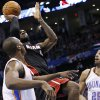 Photo - Miami Heat forward LeBron James (6) shoots between Oklahoma City Thunder forward Serge Ibaka (9) and guard Thabo Sefolosha (25) during the second quarter of an NBA basketball game in Oklahoma City, Thursday, Feb. 20, 2014. (AP Photo/Sue Ogrocki)