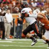 Oklahoma State\'s Clint Chelf (10) passes the ball to Desmond Roland (26) to avoid a sack by UT\'s Jackson Jeffcoat (44) in the first quarter during a college football game between the Oklahoma State University Cowboys (OSU) and the University of Texas Longhorns (UT) at Darrell K Royal - Texas Memorial Stadium in Austin, Texas, Saturday, Nov. 16, 2013. Photo by Nate Billings, The Oklahoman
