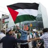Photo - A Palestinian supporter waves a flag as others create a human barricade shielding them from opposing Israeli supporters during a rally protesting the war between Israel and Hamas members in the Gaza Strip in Toronto on Saturday, July 26, 2014. (AP Photo/The Canadian Press, Darren Calabrese)