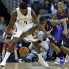 Photo - New Orleans Pelicans small forward Al-Farouq Aminu (0) and Phoenix Suns point guard Eric Bledsoe (2) battle for a loose ball in the first half of an NBA basketball game in New Orleans, Tuesday, Nov. 5, 2013. (AP Photo/Gerald Herbert)