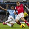 Photo - Manchester City's Fernandinho, left, fights for the ball against Arsenal's Jack Wilshere during their English Premier League soccer match at the Etihad Stadium, Manchester, England, Saturday Dec. 14, 2013. (AP Photo/Jon Super)