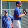 Photo - Chicago Cubs manager Rick Renteria, left, watches pitcher Travis Wood throw during the team's first spring training baseball practice, Friday, Feb. 14, 2014, in Mesa, Ariz. (AP Photo/Matt York)