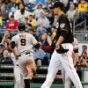 Photo - San Francisco Giants' Brandon Belt (9) scores on a sacrifice fly to center by Giants' Ehire Adrianza as Pittsburgh Pirates starting pitcher Charlie Morton, right, walks back to the mound during the second inning of a baseball game in Pittsburgh, Tuesday, May 6, 2014. (AP Photo/Gene J. Puskar)