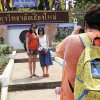 """Photo - In this March 30, 2014 photo, Chinese tourists pose for a photograph at the main entrance to Chiang Mai University in Chiang Mai province, northern Thailand. The bucolic, once laid-back campus of one of Thailand's top universities is under a security clampdown. Not against a terrorist threat, but against Chinese tourists. Thousands have clambered aboard student buses at the university, made a mess in cafeterias and sneaked into classes to attend lectures. Someone even pitched a tent by a picturesque lake. The reason: """"Lost in Thailand,"""" 2012 slapstick comedy partly shot on campus that is China's highest-grossing homegrown movie ever. (AP Photo/Apichart Weerawong)"""