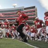 Nebraska\'s retiring athletic director and former coach Tom Osborne runs onto the field with players prior to an NCAA college football game against Minnesota, in Lincoln, Neb., Saturday, Nov. 17, 2012. Osborne is being honored for his involvement in 500 Nebraska football games. (AP Photo/Dave Weaver)