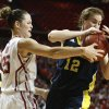 Oklahoma\'s Whitney Hand (25) fights with Michigan\'s Kate Thompson (12) for the ball during a first round game of the NCAA women\'s basketball tournament between the University of Oklahoma Sooners and the Michigan Wolverines at Lloyd Noble Center in Norman, Okla., Sunday, March 18, 2012. Oklahoma won 88-67. Photo by Bryan Terry, The Oklahoman