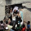 A man who was trapped in an eight-story building housing several garment factories is rescued after the structure collapsed in Savar, near Dhaka, Bangladesh, Wednesday, April 24, 2013. The building collapsed near Bangladesh\'s capital Wednesday morning, killing dozens of people and trapping many more in the rubble, officials said. (AP Photo/ A.M. Ahad)