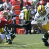 Photo - Green Bay Packers quarterback Aaron Rodgers (12) tries to run from San Francisco 49ers linebacker Aldon Smith (99) during the first quarter of an NFL football game, Sunday, Sept. 8, 2013, in San Francisco. Smith sacked Rodgers on the play. (AP Photo/Jeff Chiu)
