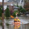 Boro Sangulin paddles a kayak through a flooded 16th Street from the effects of superstorm Sandy in Bayville, N.Y., on Tuesday, Oct., 30, 2012. Sangulin was checking on the flood damage of his home at the end of the block. (AP Photo/Kathy Kmonicek) ORG XMIT: NYKK107