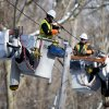Photo - Linesmen work to restore electrical power, Friday, Feb. 7, 2014, in Downingtown, Pa. A small army of electricity restoration crews labored Friday to reconnect about 330,000 customers in Pennsylvania and Maryland.  (AP Photo/Matt Rourke)