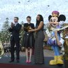 Walt Disney World Parks and Resorts Chairman Tom Staggs, left, and the character Mickey Mouse, right, applaud as actress Ginnifer Goodwin, second from left, and singer Jordin Sparks cut the ceremonial ribbon for the New Fantasyland attraction at the Walt Disney World Resort\'s Magic Kingdom theme park in Lake Buena Vista, Fla., Thursday, Dec. 6, 2012. The new attraction is the largest expansion at the Magic Kingdom.(AP Photo/Phelan M. Ebenhack)