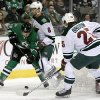 Photo - Dallas Stars' Shawn Horcoff (10) fights Minnesota Wild defenseman Marco Scandella (6) and defenseman Jonas Brodin (25) for control of the puck in the first period of an NHL hockey game, Tuesday, Jan. 21, 2014, in Dallas. (AP Photo/Tony Gutierrez)