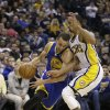 Photo - Golden State Warriors' Stephen Curry (30) goes to the basket against Indiana Pacers' George Hill (3) during the first half of an NBA basketball game Tuesday, March 4, 2014, in Indianapolis. (AP Photo/Darron Cummings)