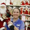 Photo - Hobby Lobby worker Lydia Wells shows off just one of the many Santas at Hobby Lobby, 3160 S Broadway in Edmond.  DOUG HOKE - THE OKLAHOMAN