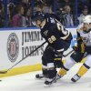 St. Louis Blues\' Ian Cole (28) reaches for the puck next to Nashville Predators\' Colin Wilson (33) during the first period of an NHL hockey game Saturday, Feb. 1, 2014, in St. Louis. (AP Photo/Bill Boyce)