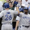 Photo -   Toronto Blue Jays' Adam Lind, left, celebrates with Rajai Davis after hitting a solo home run against the Chicago White Sox during the second inning of a baseball game in Chicago, Friday, July 6, 2012. (AP Photo/Nam Y. Huh)