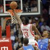Photo - Houston Rockets guard James Harden (13) drives to the basket between Oklahoma City Thunder guard Russell Westbrook (0) and forward Serge Ibaka (9) during the first half of an NBA basketball game, Saturday, Dec. 29, 2012, in Houston. (AP Photo/Bob Levey)
