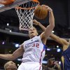 Photo - Los Angeles Clippers forward Blake Griffin, left, grabs a rebound away from New Orleans Pelicans center Alexis Ajinca, of France, during the first half of an NBA basketball game, Saturday, March 1, 2014, in Los Angeles. (AP Photo/Mark J. Terrill)