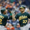 Photo - Oakland Athletics' Brandon Moss is greeted by Yoenis Cespedes after his solo home run during the fifth inning of Game 3 of an American League baseball division series against the Detroit Tigers in Detroit, Monday, Oct. 7, 2013. (AP Photo/Paul Sancya)