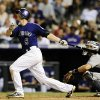 Photo - Colorado Rockies DJ LeMahieu hits a double in the third inning of a baseball game against the San Diego Padres on Monday, Aug. 12, 2013, in Denver. (AP Photo/Chris Schneider)