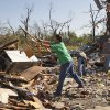 Stephen Eldridge throws rubble on a pile as he helps clean up the remains of two relatives homes, in Tushka, Okla., Friday, April 15, 2011. The home crashed together during last night\'s tornadoes. (AP Photo/Sue Ogrocki)