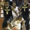 Photo - Texas's Jonathan Holmes, right, and Vanderbilt's Rod Odom try to gain possession of a loose ball during the first half of an NCAA college basketball game in Austin, Texas, on Monday, Dec. 2, 2013. (AP Photo/Austin American-Statesman, Deborah Cannon)