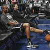 Brooklyn Nets center Jason Collins sits in a courtside seat after warming up for the Nets\' NBA basketball game against the Denver Nuggets in Denver on Thursday, Feb. 27, 2014. (AP Photo/David Zalubowski)