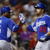 Photo - Los Angeles Dodgers' Adrian Gonzalez (23) is congratulated by Juan Uribe (5) after hitting a solo home run against the Cincinnati Reds in the sixth inning during an exhibition baseball game in Goodyear, Ariz., Wednesday, March 5, 2014. (AP Photo/Paul Sancya)