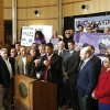 Photo - Sacramento Mayor Kevin Johnson speaks while surrounded by investors, public officials and fans during a news conference to introduce the first part of his four-step plan to keep the Sacramento Kings NBA basketball team in Sacramento, Calif., on Tuesday, Jan. 22, 2013. Johnson, who said he has 19 local investors who have pledged at least $1 million each to buy the franchise, made his announcement a day after the Maloof family announced it has signed an agreement to sell the Kings to a Seattle group led by investor Chris Hansen. (AP Photo/Rich Pedroncelli)