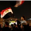 A young Egyptian boy waves a national flag from his mother\'s shoulders as protesters chant slogans in Tahrir Square in Cairo, Egypt, Tuesday, Dec. 4, 2012. A protest by tens of thousands of Egyptians outside the presidential palace in Cairo turned violent on Tuesday as tensions grew over Islamist President Mohammed Morsi\'s seizure of nearly unrestricted powers Thousands of protesters also gathered in Cairo\'s downtown Tahrir Square, miles away from the palace, to join several hundred who have been camping out there for nearly two weeks. (AP Photo/Maya Alleruzzo)