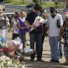Actor Christian Bale, holding flowers at center, joins hands and prays with visitors to a memorial to the victims of Friday\'s mass shooting, Tuesday, July 24, 2012, in Aurora, Colo. Twelve people were killed when a gunman opened fire during a late-night showing of the movie