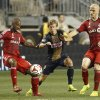 Photo - Toronto FC's Collen Warner, left, goes after the ball as teammate Michael Bradley, right, tries to help against Philadelphia Union's Brian Carroll, center, during the first half of an MLS soccer match, Wednesday, Sept. 3, 2014, in Chester, Pa. (AP Photo/Chris Szagola)