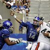Photo - Kentucky quarterback Patrick Towles (14) passes under pressure from Tennessee-Martin defensive lineman Matt Murphy (48), right,  in the first half of an NCAA college football game in Lexington, Ky., Saturday, Aug. 30, 2014. At left is Kentucky lineman Ramsey Meyers (69). (AP Photo/Garry Jones)