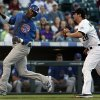 Chicago Cubs\' Junior Lake, left, runs from Colorado Rockies third baseman Nolan Arenado before being tagged out during a rundown between third base and home plate in the second inning of a baseball game in Denver, Friday, July 19, 2013. (AP Photo/Joe Mahoney)