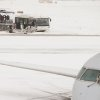 Passengers board a small plane outside on a snowy Presidents Day at Washington\'s Ronald Reagan National Airport Monday, Feb. 15, 2016. (AP Photo/Andrew Harnik)