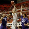 Oklahoma State\'s Markel Brown (22) goes for a rebound between Kansas State\'s Rodney McGruder (22) and Adrian Diaz (20) during an NCAA college basketball game between the Oklahoma State University Cowboys (OSU) and the Kansas State University Wildcats (KSU) at Gallagher-Iba Arena in Stillwater, Okla., Saturday, Jan. 21, 2012. Photo by Bryan Terry, The Oklahoman