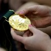 A student holds one of Shannon Miller\'s gold medals as she speaks during the grand opening of the new Star Gymnastics facilities in Edmond on Monday, Feb. 23, 2009. By John Clanton, The Oklahoman