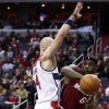 Photo - Miami Heat forward LeBron James (6) looks to pass around Washington Wizards center Marcin Gortat (4), from Poland, in the first half of an NBA basketball game on Wednesday, Jan. 15, 2014, in Washington. (AP Photo/Alex Brandon)