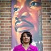 In this Tuesday, Jan. 8, 2013 photo, Bernice King stands in the King Center next to a banner hanging in memory of her father, Dr. Martin Luther King Jr., in Atlanta. The legacy of the civil rights movement has long been invoked when people talk about the nation\'s first black president, and this year the memory of the Rev. Martin Luther King Jr. and the life of President Barack Obama will overlap significantly for a day. For only the second time, the presidential inauguration falls on the Rev. Martin Luther King Jr. holiday. (AP Photo/David Goldman)