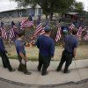 Members of the Centennial Initial Attack Fire Crew, from Island Park, Idaho, pay their respects at a memorial outside the Granite Mountain Interagency Hotshot Crew fire station, Thursday, July 4, 2013, in Prescott, Ariz. Nineteen firefighters from Granite Mountain Interagency Hotshot Crew were killed battling a wildfire near Yarnell, Ariz., Sunday. The elite crew of firefighters were overtaken by the out-of-control blaze as they tried to protect themselves from the flames under fire-resistant shields. (AP Photo/Chris Carlson)