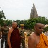 Photo - Buddhist monks and security officers walk after an explosion on the campus of the Mahabodhi Temple, the Buddhist Great Awakening temple, in Bodhgaya, about 130 kilometers (80 miles) south of Patna, the capital of the eastern Indian state of Bihar, Sunday, July 7, 2013. A series of small blasts hit three Buddhist temples in eastern India early Sunday, injuring at least two people, police said. (AP Photo/Manish Bhandari)