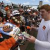 Photo - Cincinnati Bengals quarterback Andy Dalton, right, signs autographs after practice at the NFL football team's training camp on Sunday, July 28, 2013, in Cincinnati.  (AP Photo/Al Behrman)