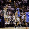 Oklahoma City's Serge Ibaka, center, charges at San Antonio's Tony Parker as he shoots the game-winning basket during Thursday's game in San Antonio. AP PHOTO