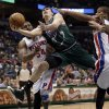 Photo - Milwaukee Bucks' Ersan Ilyasova is fouled as he drives between Detroit Pistons' Jason Maxiell (54) and Greg Monroe during the second half of an NBA basketball game Saturday, Feb. 9, 2013, in Milwaukee. (AP Photo/Morry Gash)